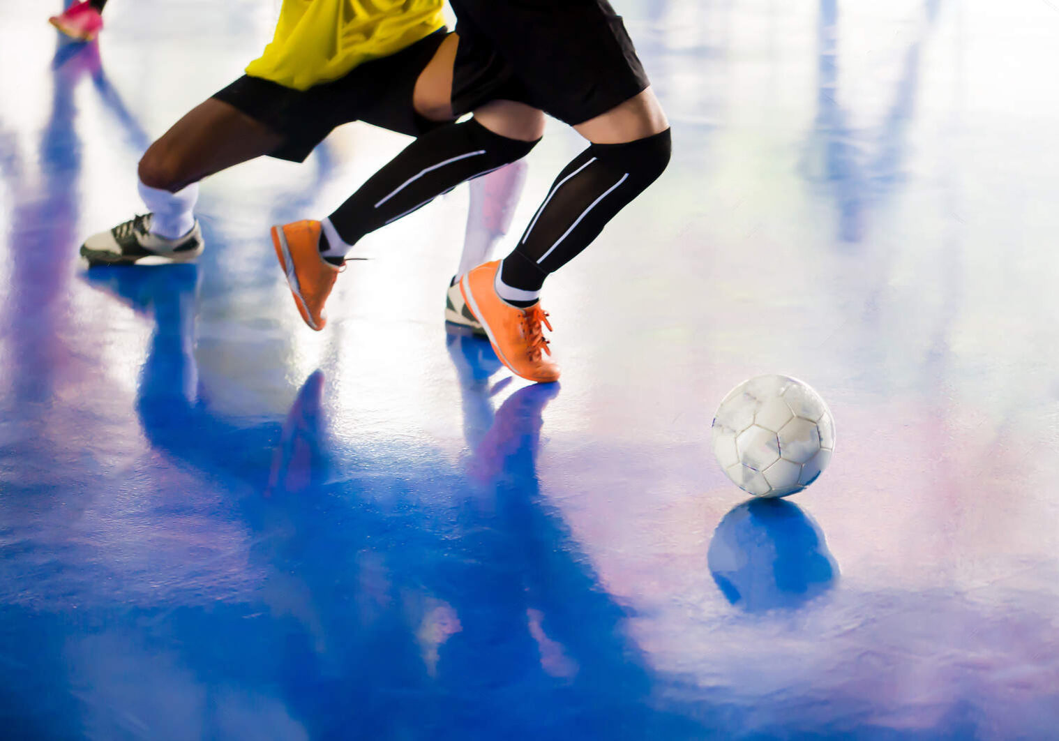 Futsal player  trap and control the ball for shoot to goal. Soccer players fighting each other by kicking the ball. Indoor soccer sports hall. Football futsal player, ball, futsal floor. Sports background. Youth futsal league. Indoor football players with classic soccer ball.
